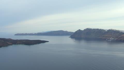 ws aerial view of ocean to santorini with sailboat / santorini, cyclades, greece - santorini stock videos & royalty-free footage
