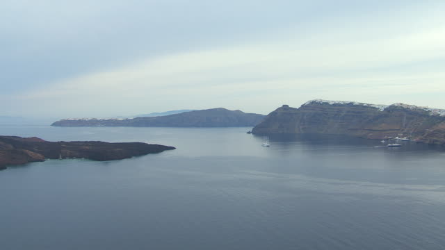 ws aerial view of ocean to santorini with sailboat / santorini, cyclades, greece - santorini stock videos and b-roll footage