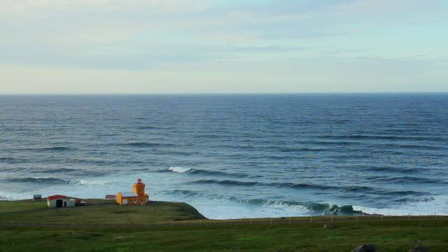 ws view of ocean waves crashing against cliff toward with small yellow barn on top of cliff / skagafjorour, nordhurland vestra, iceland  - wiese stock videos & royalty-free footage