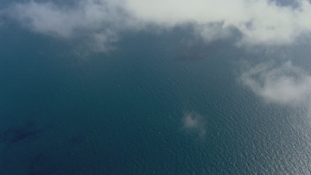 WS AERIAL View of ocean with helicopter flying through clouds / Queensland, Australia