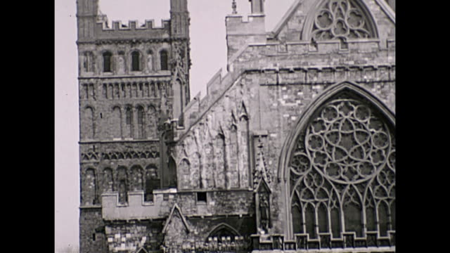 view of of exeter cathedral in the mid 1930s with period cars and people walking by the door / filmed pre ww2 before the building was largely... - exeter cathedral stock videos & royalty-free footage