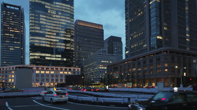 ws view of office building and taxi stand in station at dusk / chiyoda, tokyo, japan - taxi stand stock videos and b-roll footage