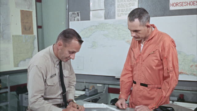 ms cu view of officer and pilot study reconnaissance photograph / pisa, italy - anno 1960 video stock e b–roll
