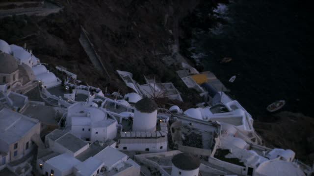 stockvideo's en b-roll-footage met aerial ws ds  view of oia island village and windmill at twilight  / santorini, oia, cyclades islands, greece - oia santorini