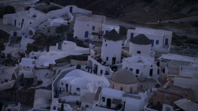 aerial ws ds view of oia island village part of santorini at twilight / santorini, oia, cyclades islands, greece - oia santorini stock videos & royalty-free footage