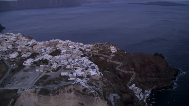 stockvideo's en b-roll-footage met aerial ws view of oia island villageat twilight / santorini, oia, cyclades islands, greece - oia santorini