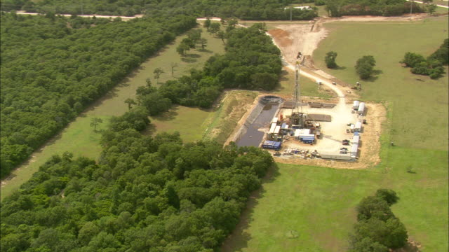 vidéos et rushes de ms aerial zo view of oil drilling rig surrounded by trees / texas, united states - tour de forage