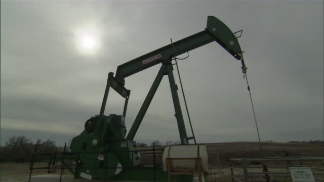 ws view of oil pump jack with sun in background / college station, texas, usa - texas stock videos & royalty-free footage