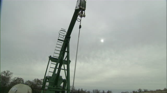 vidéos et rushes de ws view of oil pump jack with sun in background / college station, texas, usa - tour de forage