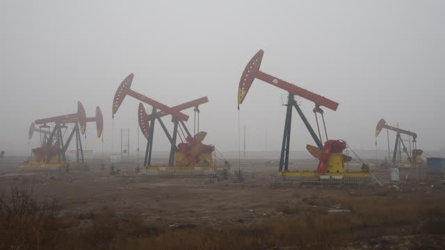 vídeos y material grabado en eventos de stock de a view of oil pumping units in smog on jan 06 2017 at dagang oilfield in tianjin china - estación de bombeo