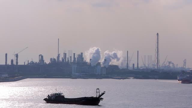 vídeos y material grabado en eventos de stock de ms pan view of oil refinery with ship in foreground / singapore - buque tanque