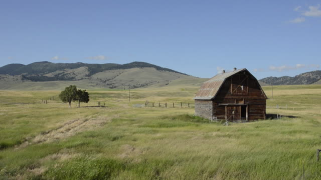 stockvideo's en b-roll-footage met ws view of old barn in open field / butte, montana, united states - boerderijschuur