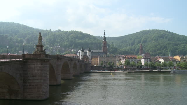ms pan view of old bridge on river in city and castle in background / heidelberg, baden-wuerttemberg, germany  - heidelberg castle stock videos & royalty-free footage