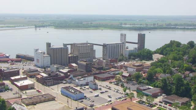 WS AERIAL POV View of old ConAgra Flour Mill with city and cars moving on road, Mississippi River in background / Alton, Illinois, United States