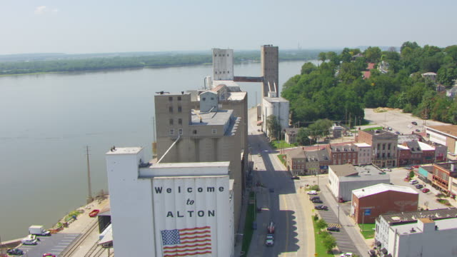 ws aerial pov view of old conagra flour mill with city and cars moving on road, mississippi river in background / alton, illinois, united states - flour mill stock videos & royalty-free footage
