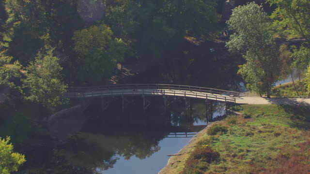 ws aerial pov view of old north bridge near by minuteman statue / concord, massachusetts, united states - minuteman statue lexington stock videos & royalty-free footage