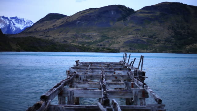 ms view of old pier going out into water on blue lake with mountains   / torres del paine, chilean patagonia, chile - patagonia chile stock videos and b-roll footage
