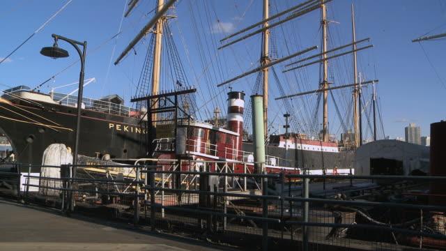 vídeos de stock e filmes b-roll de ws view of old ships anchored at south street sea port in manhattan / new york city, new york, usa - ancorado