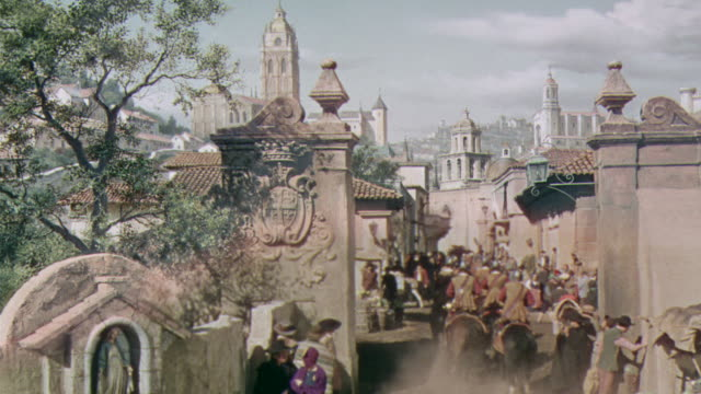 ws ha view of old spanish town or village with people ride through on horse and carriage others on foot - historical reenactment stock-videos und b-roll-filmmaterial
