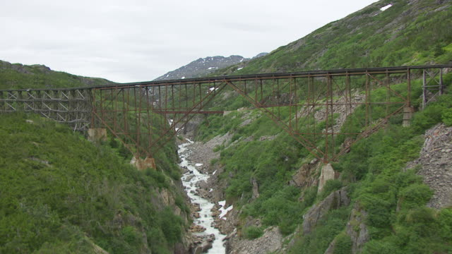 vídeos de stock, filmes e b-roll de ws aerial view of old steel bridge with skagway river / alaska, united states - skagway