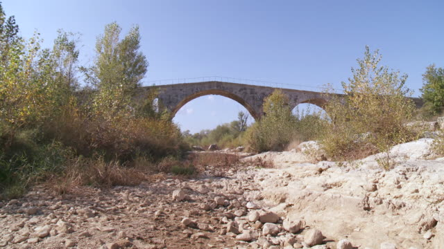 ms view of old three arched bridge over dry rocky river bed / apt, provence, france - apt stock videos and b-roll footage