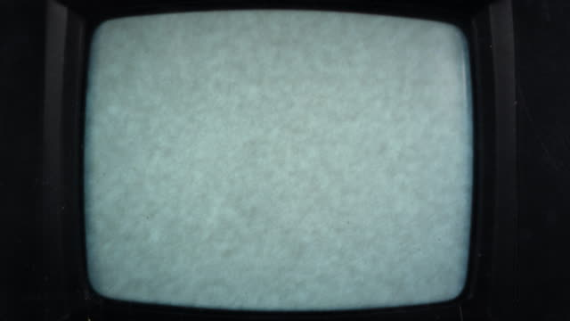 view of old tv screen as it warms up to static screen - tubo video stock e b–roll