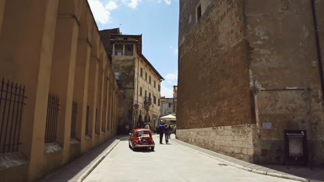 ws view of old vintage fiat 500 crossing square in pitigliano - tuscany stock videos & royalty-free footage