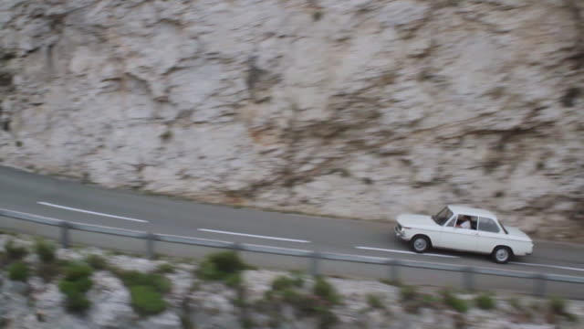 WS AERIAL TS View of old white car driving fast up a windy mountain road with cliffs and tunnels / greolieres, cote d'azur, france