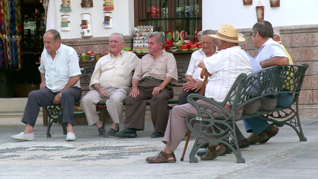 ms view of older people seating on bench in front of shop at mountain village mijas / mijas, andalusia, spain - sitting video stock e b–roll