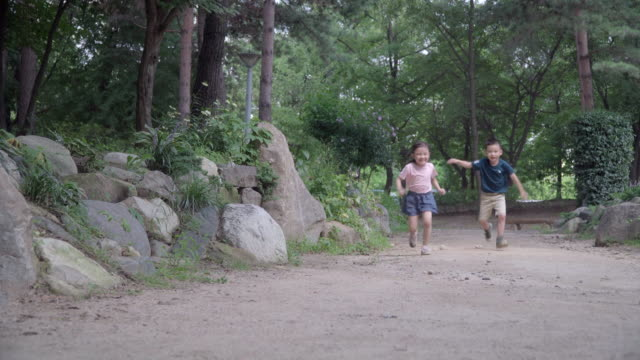 vídeos de stock, filmes e b-roll de view of one girl and one boy running with backpacks in summer at seoulforest (the third largest park in seoul city) - cabelo preso