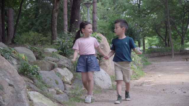 view of one girl and one boy walking hand in hand in summer at seoulforest (the third largest park in seoul city) - unschuld stock-videos und b-roll-filmmaterial