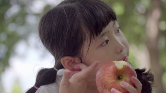 View of one girl eating an apple in summer at Seoulforest (the third largest park in Seoul city)