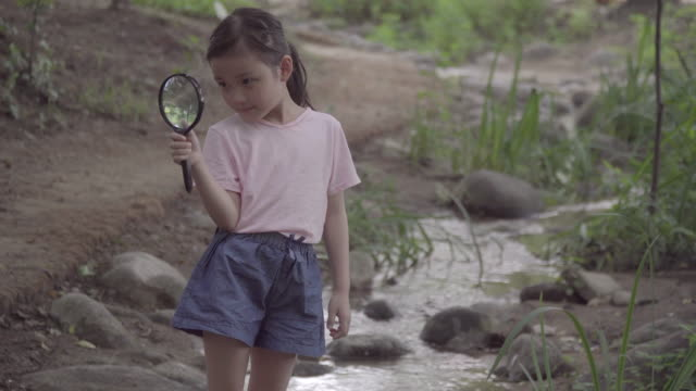 View of one girl holding a magnifying glass with smile in summer at Seoulforest (the third largest park in Seoul city)