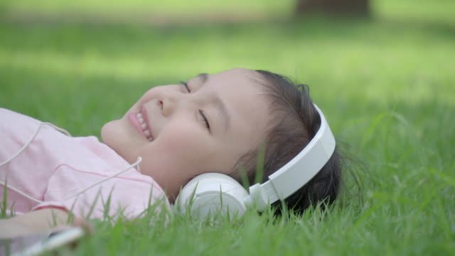 view of one girl lying on the lawn with a headphone in summer at seoulforest (the third largest park in seoul city) - lying on back stock videos and b-roll footage