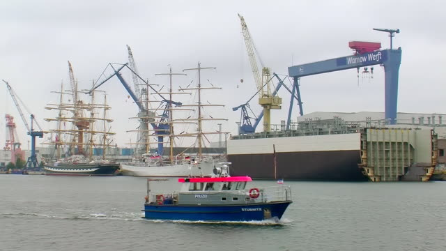 ws view of one police boat moving in front of big sail boat at warnemunde harbor near rostock / warnemunde, mecklenburg vorpommern, germany - police boat stock videos and b-roll footage