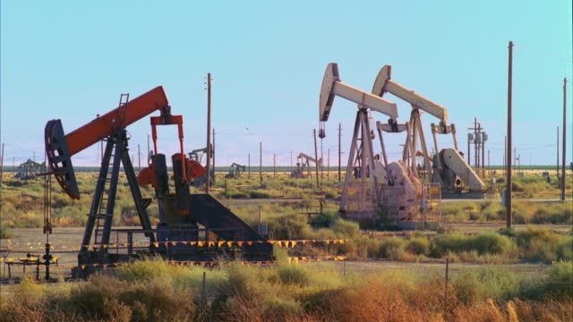 ws view of one red and two white oil wells pumping / san joaquin valley, california, united states    - pump jack stock videos & royalty-free footage