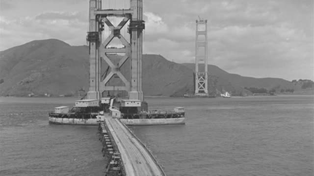 ws view of one small boat flowing from middle of golden gate bridge under construction - golden gate bridge stock videos & royalty-free footage