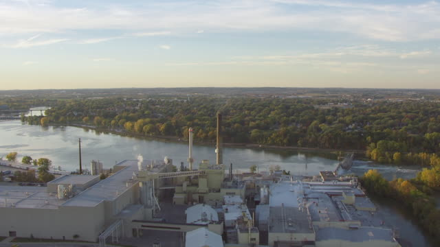 MS AERIAL View of orbit around Appleton Coated Paper Company to sun setting / Appleton, Wisconsin, United States