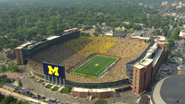 WS AERIAL View of orbit around Michigan Stadium with fans in stadium wearing yellow / Ann Arbor, Michigan, United States