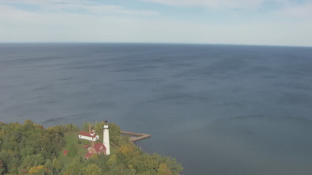 ms aerial view of orbit around outer island lighthouse with lake superior / wisconsin, united states  - lago superiore video stock e b–roll