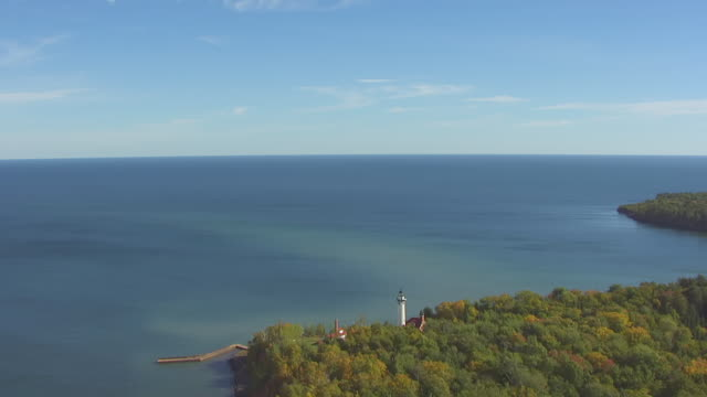 ws aerial view of orbit around outer island lighthouse with lake superior / wisconsin, united states  - lago superiore video stock e b–roll