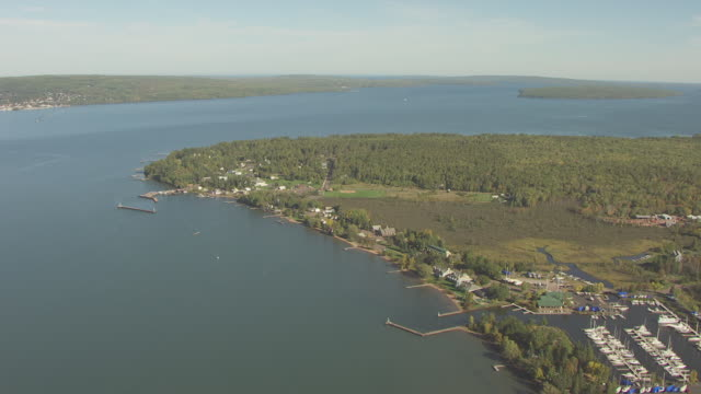 ws aerial view of orbit around tip of madeline island for views of forest interior and lake superior / wisconsin, united states  - lago superiore video stock e b–roll