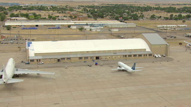 ws aerial ds view of orbit hangar eighty four with airplanes parked outside - roswell stock videos & royalty-free footage