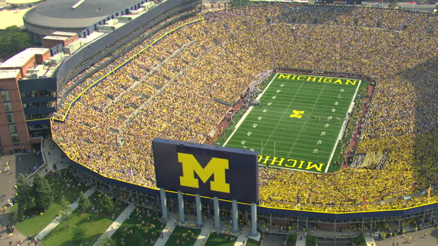 ms aerial view of  orbit michigan stadium with fans in stadium wearing yellow and football players on field / ann arbor, michigan, united states - 10 seconds or greater stock videos & royalty-free footage
