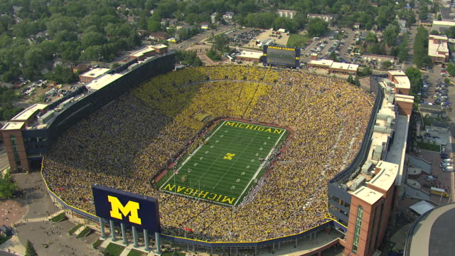 WS AERIAL View of orbit Michigan Stadium with football players on field and fans filling seats / Ann Arbor, Michigan, United States