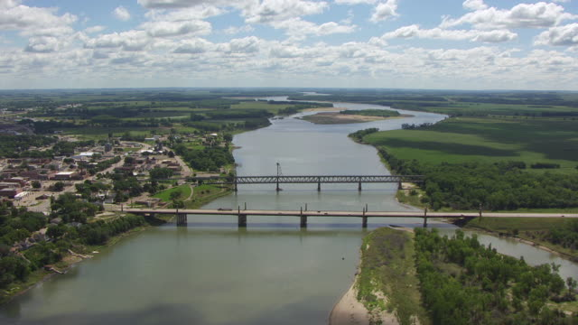 WS AERIAL View of orbit town with blue sky with white clouds over Missouri River / Yankton, South Dakota, United States