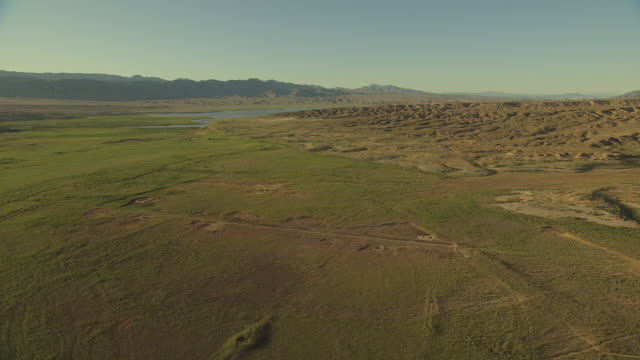 ws aerial pan view of orbit valley covered in green growth with mountains in morning sunshine / st thomas, nevada united states - ネバダ州点の映像素材/bロール