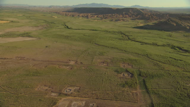 ws aerial pan view of orbit valley covered in green growth with mountains  - puebloan peoples stock videos & royalty-free footage