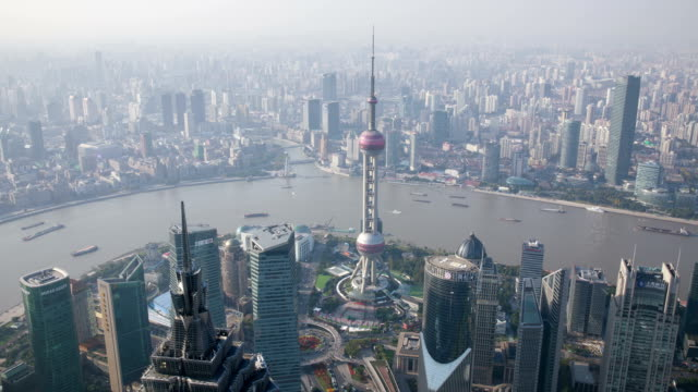 view of oriental pearl tower with skyscrapers by huangpu river from swfc tower observatory at daytime in shanghai, china - 東方明珠塔点の映像素材/bロール