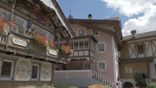 view of ornate house and village church in canazei, fassa valley, province of trento, south tyrol, italian dolomites, italy, europe - canazei video stock e b–roll